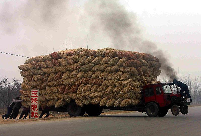 Surcharge… Des ouvriers luttent pour rééquilibrer un tracteur surchargé de sacs de maïs dans la province du Hebei, dans le nord de la Chine, lundi 14 décembre.