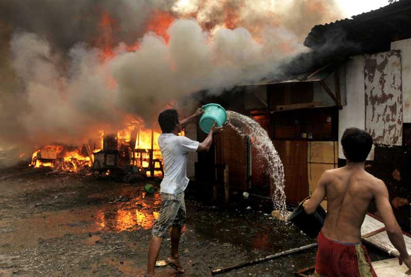 Des résidents essaient d'éteindre le feu qui s'est déclaré dans des habitations à Jakarta, en Indonésie, le 16 décembre . La cause de l'incendie n'a pas été déterminée.