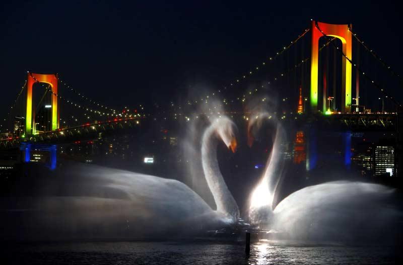 Une image de cygnes apparaît dans le ciel de Tokyo, avec, en fond, le Rainbow Bridge illuminé, le 21 décembre 2009.
