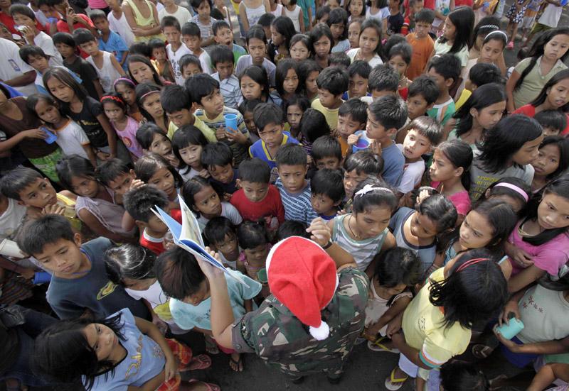 Un soldat raconte des histoires à des enfants qui ont fui le volcan Mayon, aux Philippines, le 23 décembre 2009.