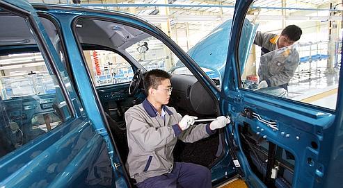 Deux ouvriers chinois montent un taxi londonien dans une usine près de Shanghaï.