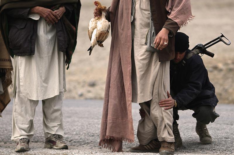 Un membre de l'ANP (police nationale afghane) fouille un villageois afghan, dimanche 3 janvier. L'armée française, appuyée par des soldats et des policiers afghans, reste toujours mobilisée dans la province de Kapisa pour retrouver les deux journalistes français de France 3 enlevés depuis six jours alors qu'ils réalisaient un reportage au nord-est de Kaboul.