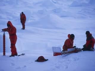 Les glaciologues, descendus sur la banquise, effectuent des analyses sous la surveillance d'un garde armé contre les ours polaires. Pendant des heures, ils vont mesurer salinité, température et épaisseur de la glace. (Philippe Bourseiller/JH Editorial)