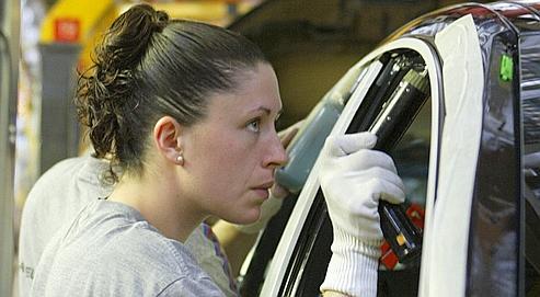 Une ouvrière dans une usine automobile. Les pathologies professionnelles du poignet peuvent être évitées par des mesures mises en œuvre sur le lieu de travail.
