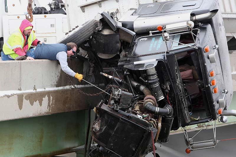 Des remorqueurs tentent de soulever la carcasse de ce camion coincé sur la barrière d'un pont à Muncie, ville de l'Indiana aux États-Unis, mercredi 17 février. Fort heureusement, le conducteur est sorti indemne de cet accident.