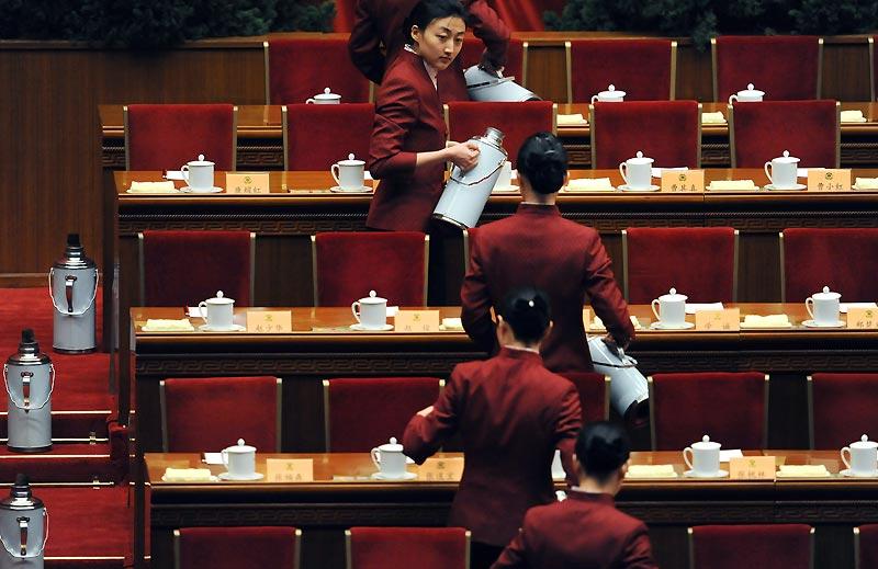 Avant l'ouverture à Pékin de la session des délégués du Peuple, des hôtesses passent dans les gradins du parlement pour préparer le rituel du thé, mercredi 3 mars.