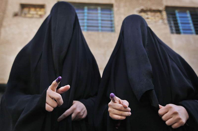 Élections en Irak. Deux femmes voilées montrent leurs doigts trempés d'encre à la sortie d'un bureau de vote de Bagdad.