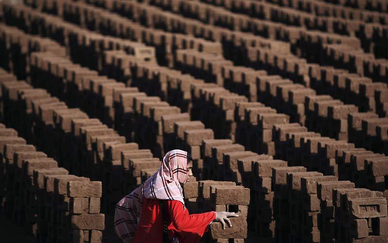 Une femme pakistanaise travaille dans une usine de fabrication de briques dans la banlieue d'Islamabad, au Pakistan, lundi 8 mars, jour de la célébration de la journée internationale des femmes.
