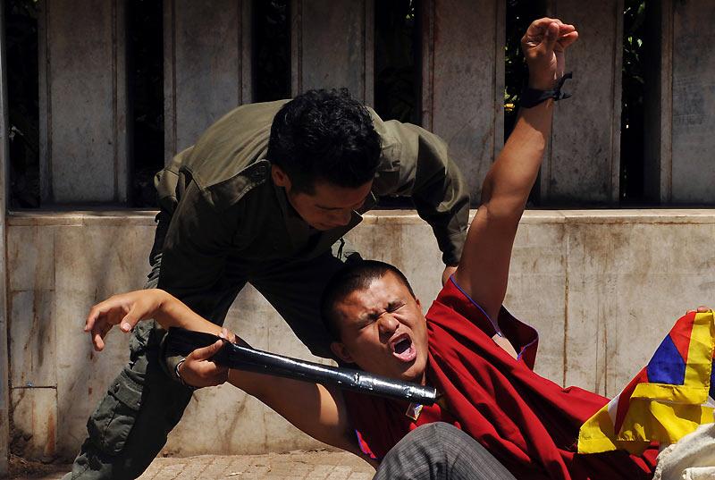 Un jeune étudiant tibétain est frappé au sol par un policier lors d'une manifestation, à Bangalore, mercredi 10 mars. Ce jour marque le 51ème anniversaire du soulèvement tibétain contre le gouvernement chinois.