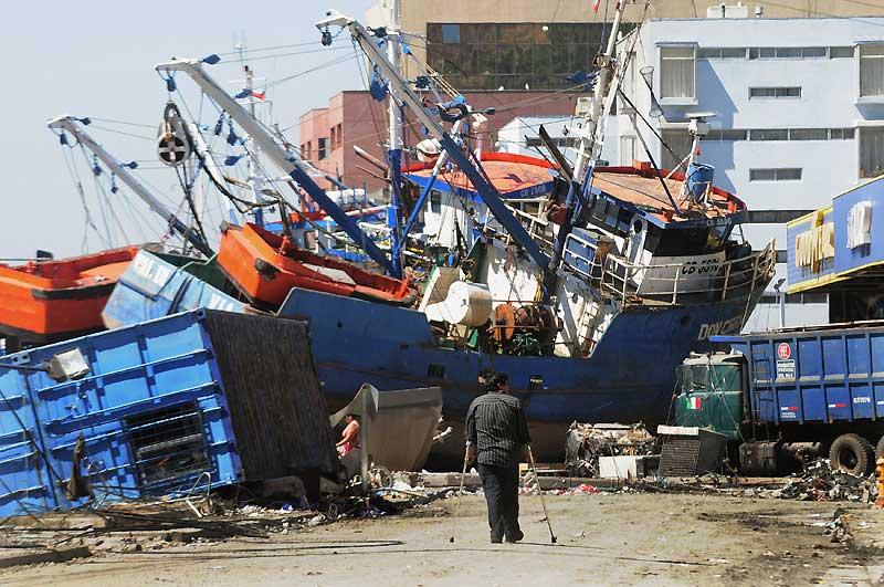 Un homme marche, le 6 mars, devant une carcasse échouée qui illustre, à elle seule, le drame du tsunami chilien de fin février. Ce chalutier gît, coque et mâts brisés, sur le chemin de terre qui conduit au village de pêcheurs d'El Morro, à Talcahuano, l'avant-port de Concepcion, deuxième ville du Chili.