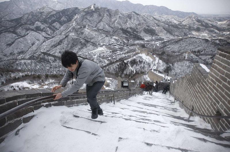 Ce touriste peine à monter les marches enneigées de la Grande Muraille de Chine, lundi 15 mars. Depuis 1987, la Grande Muraille est classée au patrimoine mondial de l'UNESCO.