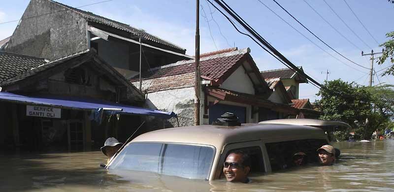 Jeudi 25 mars, à Karawang, en Indonésie. Des habitants poussent, avec le sourire, une voiture dans une rue entièrement inondée après les fortes pluies qui ont frappé cette région ces derniers jours.