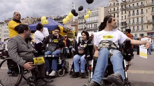 Des personnes handicapés distribuent des tracts sur le Vieux-Port à Marseille.