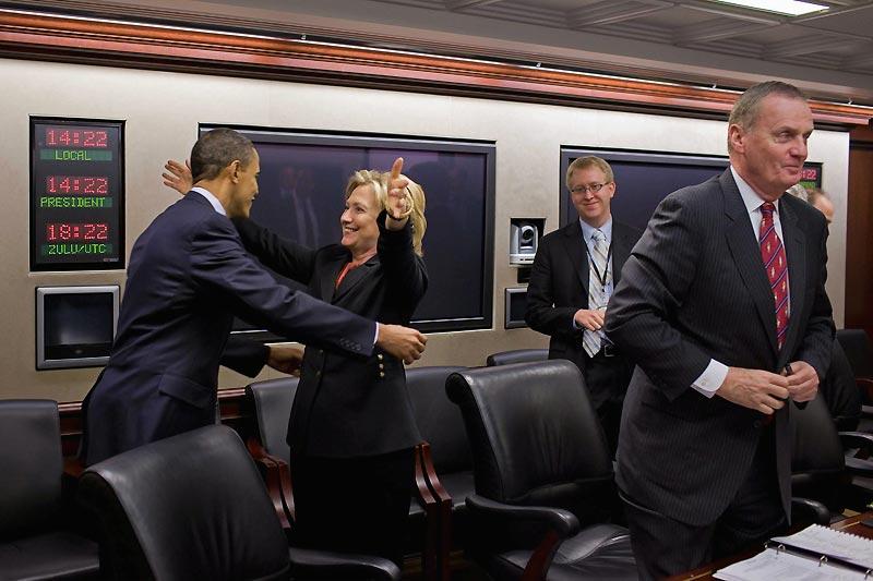 Ceci est une photo officielle de la situation room de la Maison Blanche, choisie par Washington pour illustrer la victoire d'Obama sur la question épineuse de la protection sociale aux Etats-Unis. Une embrassade à l'américaine entre le président des Etats-Unis, souvent réservé, et la démocrate de toujours, la secrétaire d'Etat Hillary Rodham Clinton. Une image détendue pour célébrer un tournant majeur dans l'histoire de la société américaine. L'occasion aussi de jeter un petit coup d'œil sur l'un des endroits les plus secrets de la Maison-Blanche où est affichée en permanence l'heure locale, l'heure du lieu où se trouve le Président et le temps universel (GMT).