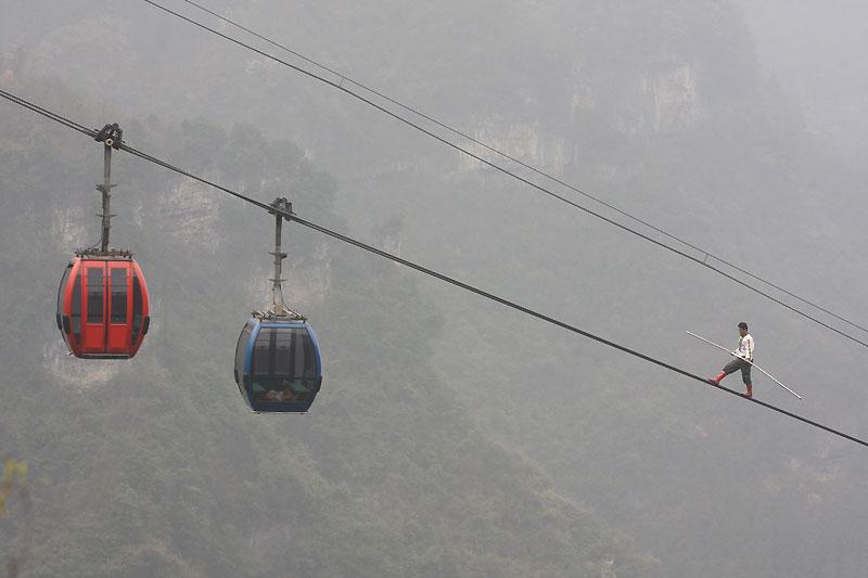 Muni de son seul balancier, cet homme marche sur le câble d'un téléphérique qui conduit au sommet de la montagne Tianzi Shan, en Chine. Ce funambule nous livre ainsi un incroyable - et tout aussi dangereux - numéro.