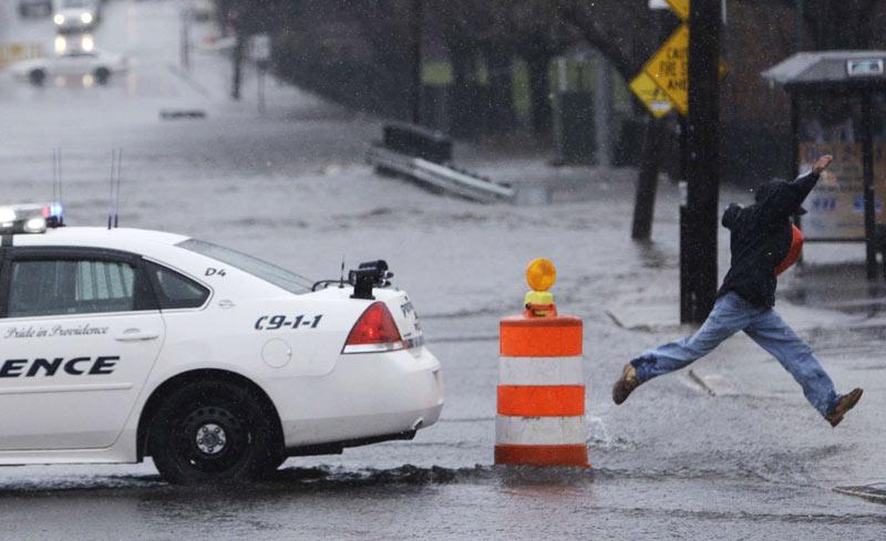 À Providence, dans l'État de Rhode Island, aux États-Unis, une rue inondée oblige un habitant à faire preuve d'un bon élan pour sauter au dessus de grandes flaques, mardi 30 mars.