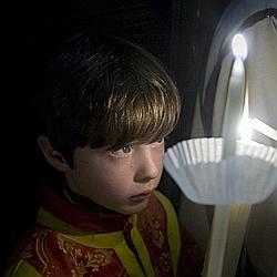 Un jeune Espagnol reçoit une bougie lors de la Pâque orthodoxe, le 18 avril 2009, à Palma de Majorque.