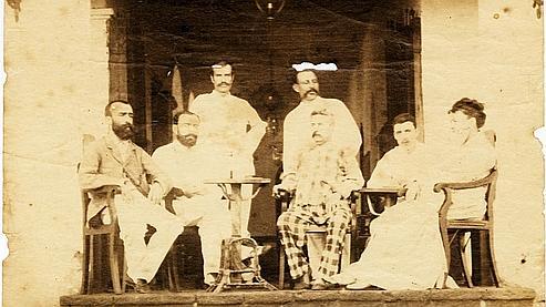 Sur le perron de l'hôtel de l'Univers à Aden en Abyssinie, Rimbaud est assis à droite, près de la femme (photo de groupe). Àgauche, le portrait tiré d'un agrandissement.