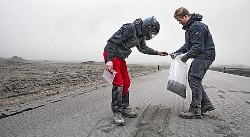 Des scientifiques ont récolté vendredi, sur une route islandaise, un échantillon de cendres volcaniques pour l'analyser.