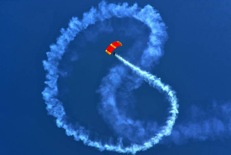 Un parachutiste de l'armée colombienne trace des figures dans le ciel avec de la fumée colorée, lors du salon Expodefensa qui s'est déroulé dimanche 18 avril, à Cali.