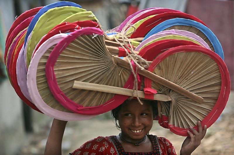 Lundi 19 avril, cette jeune fille transporte des éventails, faits main, pour les vendre sur un marché près de Dhaka, au Bangladesh.