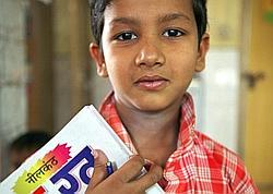 Une jeune écolier pose avec ses livres au foyer de jour de Jamghat, près de la Grande Mosquée dans la Vieille Ville de Dehli.
