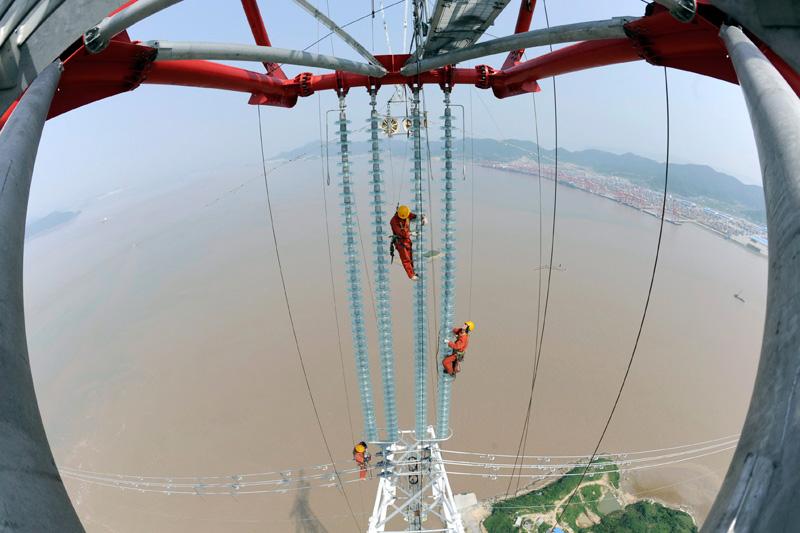 Mardi 25 mai, ces ingénieurs vérifient la bonne installation d'isolateurs sur des pylônes électriques de la ville de Hangzhou, dans la province de Zhejiang, au sud de Shanghai.