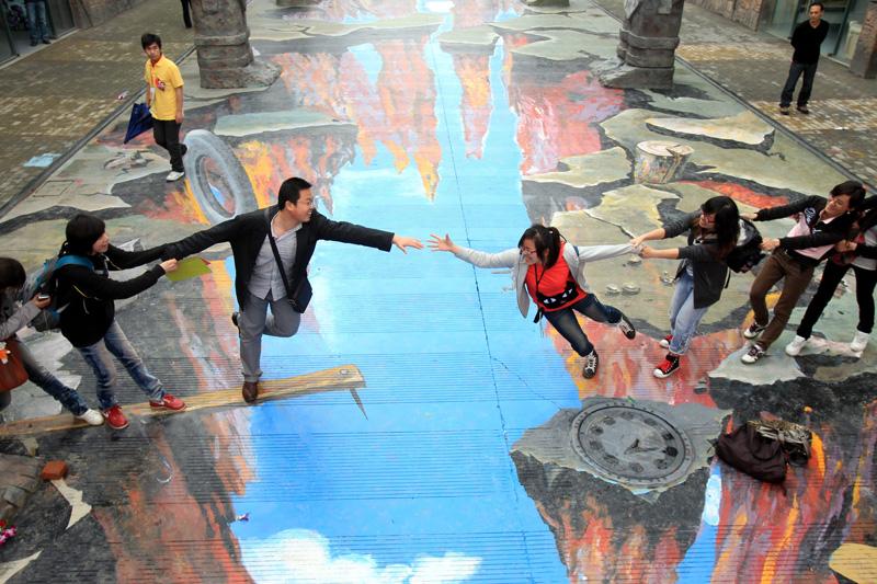 Ces visiteurs chinois posent sur une peinture en 3 dimensions réalisée sur le sol d'un parc dans la province de Hainan dans le sud de la Chine. Belle illusion d'optique !