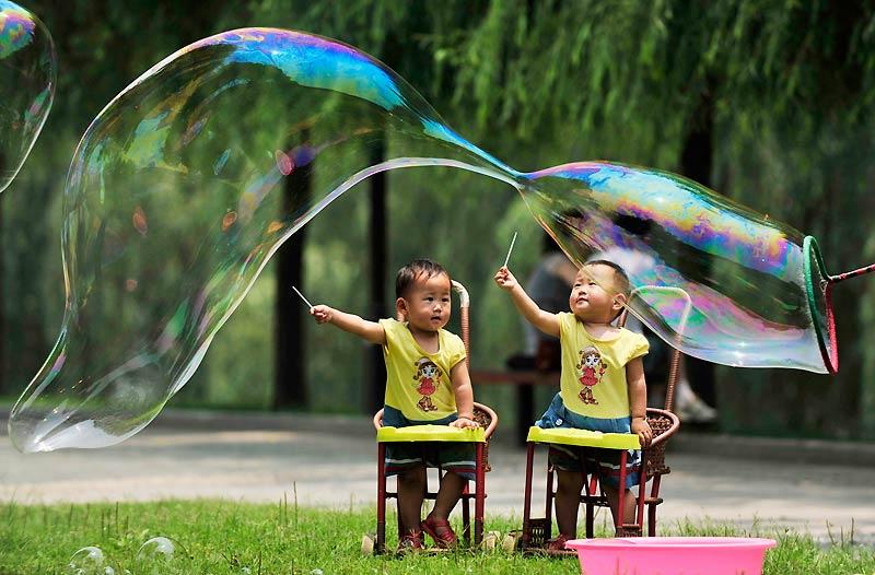 Ces enfants observent, le regard amusé, la réalisation d'une bulle de savon géante dans un parc de Wuhan, dans la province du Hubei, en Chine, au début du mois de juin.