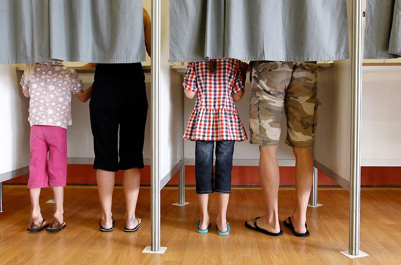 Dimanche 13 juin, des citoyens belges accompagnés de leurs enfants votent dans un bureau, à Bracle, commune située en région flamande.