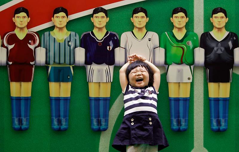 Lundi 14 juin, à Beijing, en Chine, cette petite fille rit aux éclats alors qu'elle pose devant une affiche de la Coupe du monde.