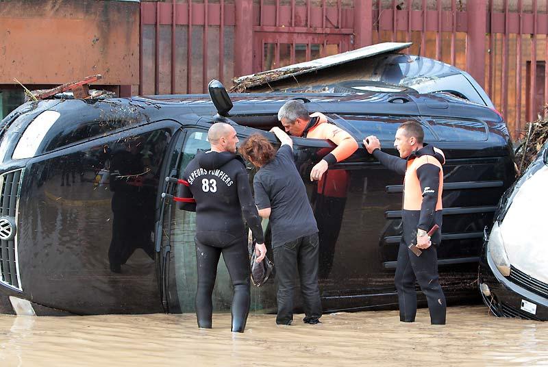 Au lendemain des importantes inondations qui se sont abattues sur Draguignan, des sauveteurs aident une femme à récupérer ses affaires personnelles restées dans sa voiture endommagée.
