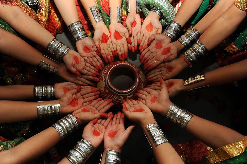 Dimanche 20 juin, à l'occasion des festivités organisées à Ahmedabad, ces femmes s'enduisent le bout des doigts et la paume de la main de couleur rouge.