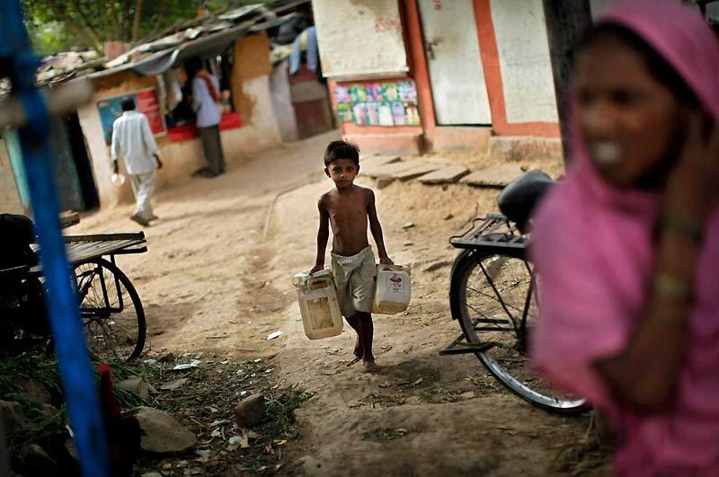 Mardi 22 juin, ce jeune enfant transporte ses bidons vides en direction d'une borne-fontaine d'eau potable pour les remplir.