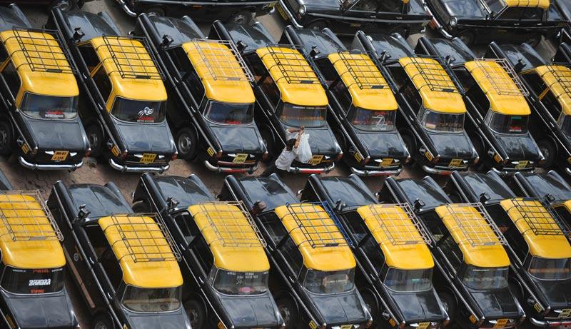 Mardi 22 juin, un homme marche au milieu de voitures garées à Mumbai, en Inde. Au total, ce sont plus de 85.000 taxis et près de 100.000 auto rickshaws qui sont restés immobilisés suite à une grève des chauffeurs qui réclament une hausse du tarif au kilomètre.
