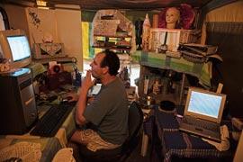 Dans une tente faite main rattachée à une caravane, Vernon Nel vérifie ses e-mails. Un modem sans fil alimente les ordinateurs. Ainsi, les six personnes vivant là peuvent-elles avoir accès à internet. (Finbarr O'Reilly/Reuters)