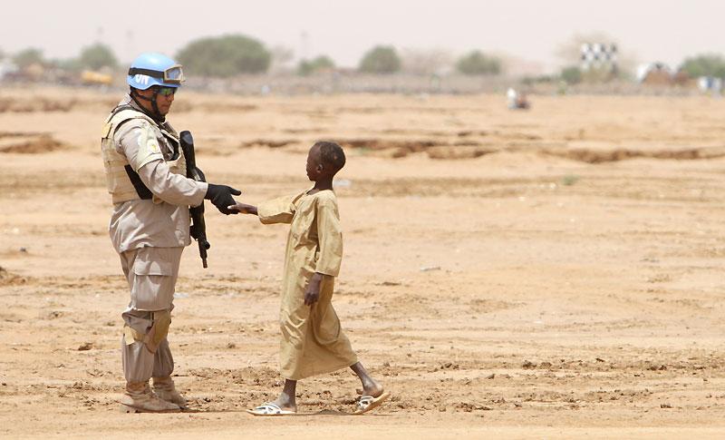 Un soldat de l'ONU serre la main à un jeune garçon à El-Fasher, capitale de la province du Darfour Nord, au Soudan, lundi 5 juillet. Le même jour, au même endroit, les participants à une conférence internationale sur la paix ont appelé les mouvements armés du pays à négocier avec le gouvernement.