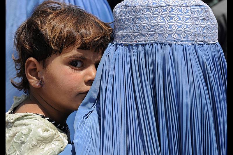 Une femme afghane porte dans ses bras un enfant dans les rues de Kaboul, mercredi 7 juillet.