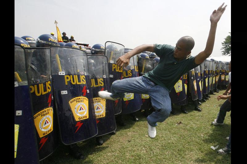 Un homme s'attaque aux forces de l'ordre lors d'une manifestation dans la ville de Manille, aux Philippines, samedi 17 juillet.
