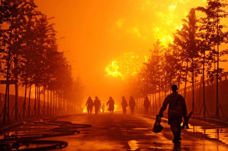 Samedi 17 juillet, des pompiers tentent de maîtriser l'incendie qui s'est déclaré au port de Xingang, à Dalian (nord-est de la Chine) suite à l'explosion de deux oléoducs. Une nappe de pétrole s'est formée sur cinquante kilomètres au large du port.