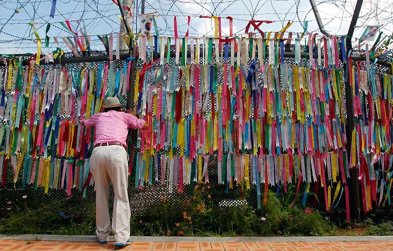 Mardi 20 juillet, cet homme observe ce qui se passe de l'autre côté de la barrière de fils barbelés décorée de rubans, près de la zone démilitarisée qui sépare les deux Corées à Paju, au nord de Séoul, en Corée du sud.