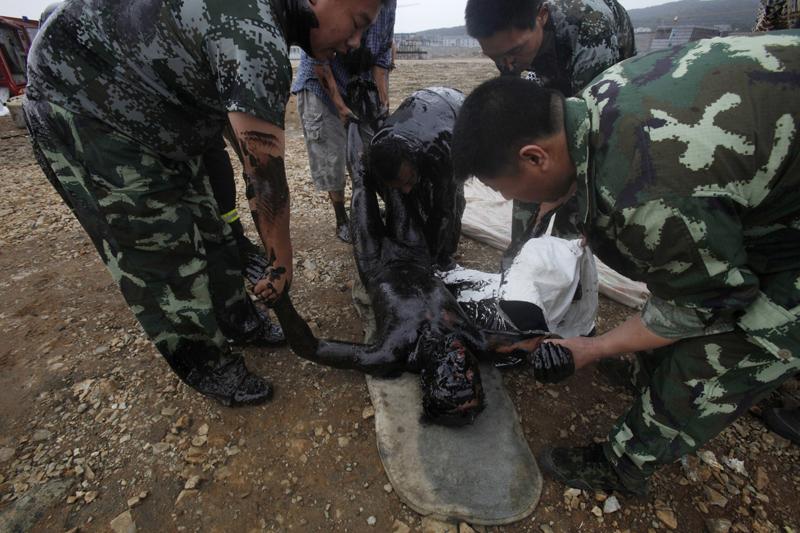 Ce pompier de 25 ans, enduit intégralement de pétrole, a réussi à  atteindre la terre ferme après être tombé d'un bateau qui participait au  nettoyage de la marée noire dans le port de Dalian, en Chine, mardi 20  juillet.