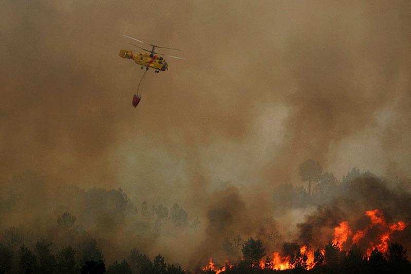 Dimanche 8 août, plus de 700 pompiers sont mobilisés pour éteindre une douzaine d'incendies qui ravagent les forêts portugaises. Un hélicoptère survole un feu à Carvalhal, près de Sao Pedro do Sul.
