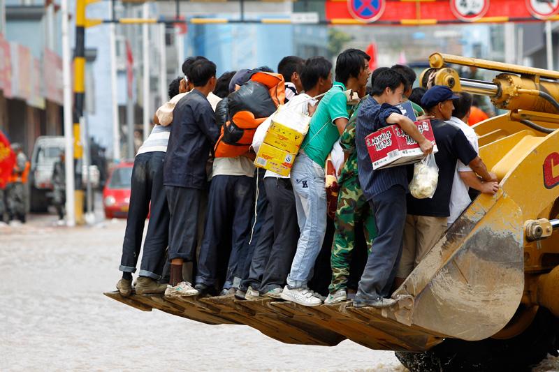 Les rues étant envahies d'eau et de boue, tous les moyens sont utilisés pour se déplacer à Zhouqu, ville de la province chinoise de Gannan. Lundi 9 août.