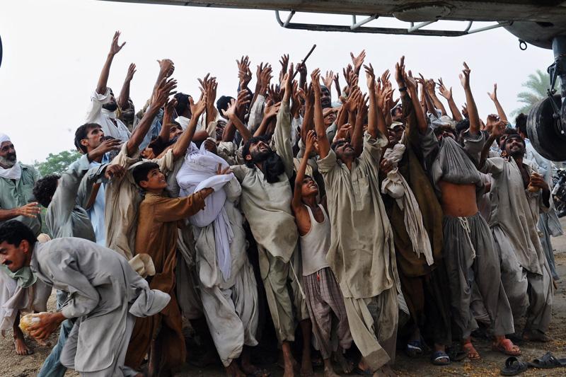 Des sinistrés pakistanais tendent les mains vers un hélicoptère salvateur qui leur apporte des provisions. Dans le pays, on dénombre au moins 15 millions de victimes des pluies diluviennes qui se sont abattues avec la mousson.