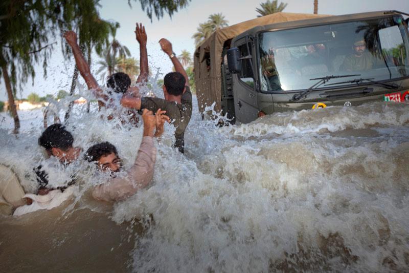 Mercredi 11 août, dans le district de Muzaffargarh, dans l'est du Pakistan, des réfugiés qui tentent de fuir les inondations croisent un camion qui amène des provisions alimentaires.