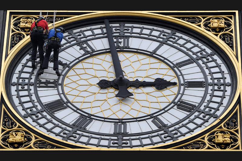 Suspendus à 70 mètres au dessus du sol, ces alpinistes urbains de l'entreprise Taskmasters travaillent sur l'horloge de Big Ben, le 12 août.