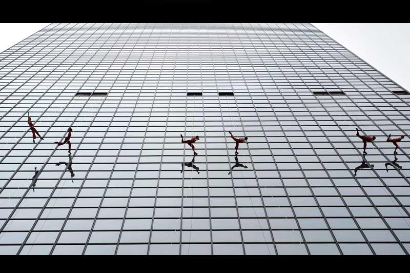 Suspendus par des filins sur la façade d'un gratte-ciel de Dallas, au Texas, ces six danseurs de la compagnie Project Bandaloop se sont donné pour mission de démontrer «la soutenable légèreté de l'être». Et ils y parviennent fort bien : leur ballet aérien se déroule avec une grâce proprement lunaire, comme en apesanteur, les pieds ne faisant que rebondir en souplesse sur les vitres entre deux sauts d'une lenteur et d'une amplitude irréelles. Un très beau spectacle, inspiré des performances du Cirque du Soleil. Et l'on ne peut s'empêcher de songer à la tête des employés de la tour, le lendemain, lorsqu'ils ont découvert des dizaines d'empreintes de pas sur leurs fenêtres !