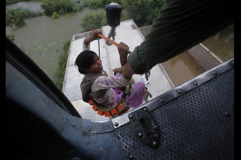 Sous les eaux. Lundi 30 août, à Sujawal, au sud du Pakistan, une femme est hélitreuillée par des membres de l'armée venus lui porter secours. Les déplacés de cette ville ont gagné Makli, où s'entassent désormais près d'un demi-million de personnes, la plupart sans rien pour s'abriter et sans eau potable ni vivres.