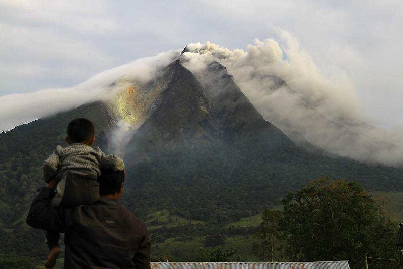 Fuite. Lundi 30 août, un homme et son fils observent le volcan du mont Sinabung, sur l'île indonésienne de Sumatra, entré en éruption la veille après 400 ans de silence. 3000 réfugiés ont été contraints de quitter leurs villages et ont été évacués vers seize centres de secours.
